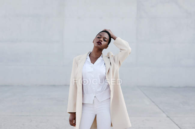 Fashion short haired model with closed eyes in white outfit posing against grey wall — Stock Photo