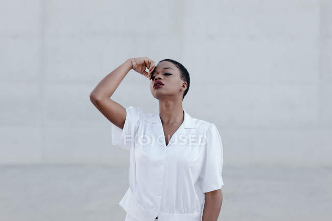 Sensual fashion short haired ethnic woman in white shirt posing against grey wall — Stock Photo