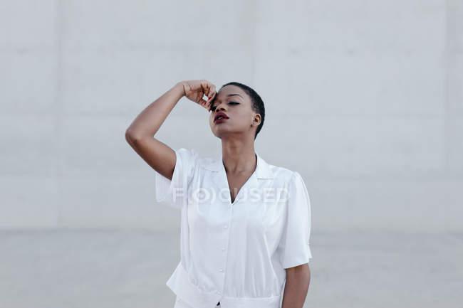Sensuale donna etnica dai capelli corti moda in camicia bianca posa contro muro grigio — Foto stock