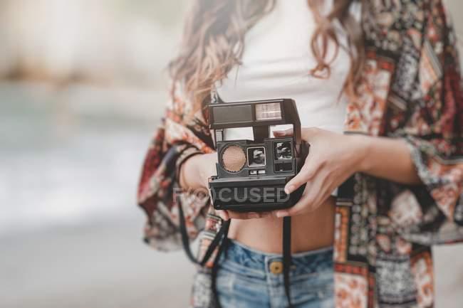 Крупним планом Жінка тримає камеру на березі на розмитому фоні — стокове фото