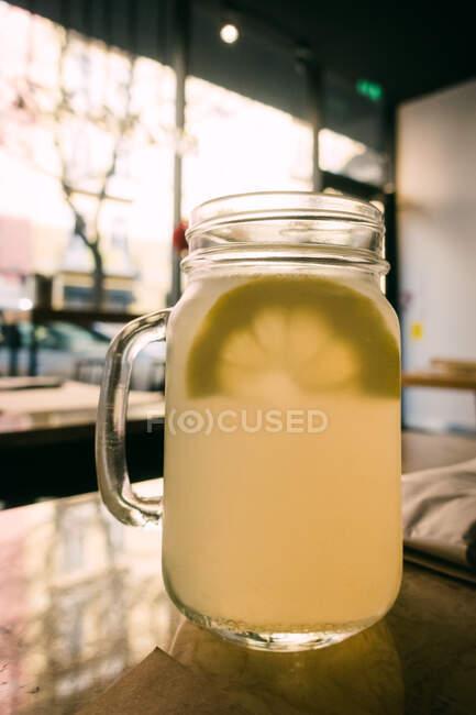 Tazas de vidrio con deliciosa bebida fresca de limón sobre fondo borroso - foto de stock