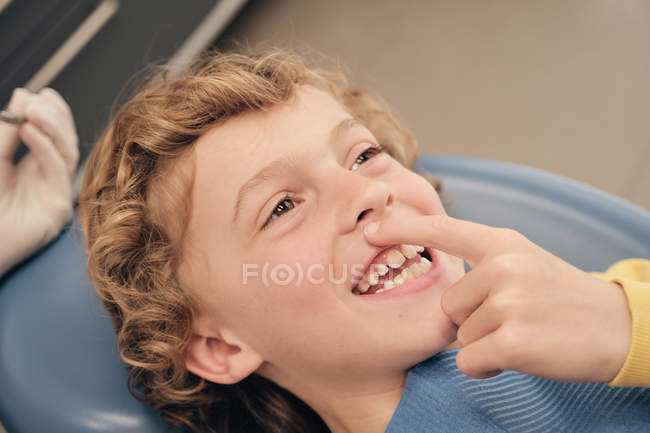 Cheerful cute boy pointing at tooth while lying on dentist chair in modern clinic — Stock Photo