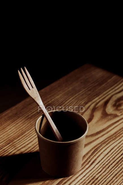 Holzgabel in Tasse auf Schreibtisch im dunklen Raum — Stockfoto