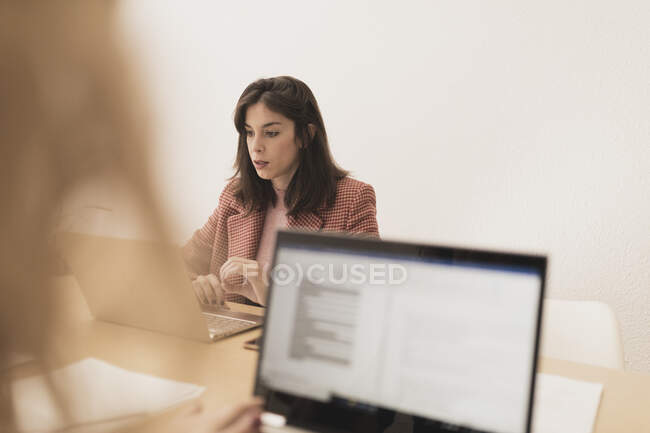 Concentrated young ladies browsing on laptops and sitting at table in office — Stock Photo