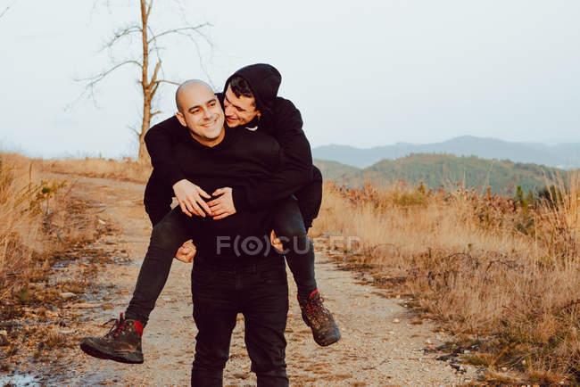 Счастливая гомосексуальная пара веселится на пути между растениями в горах — стоковое фото