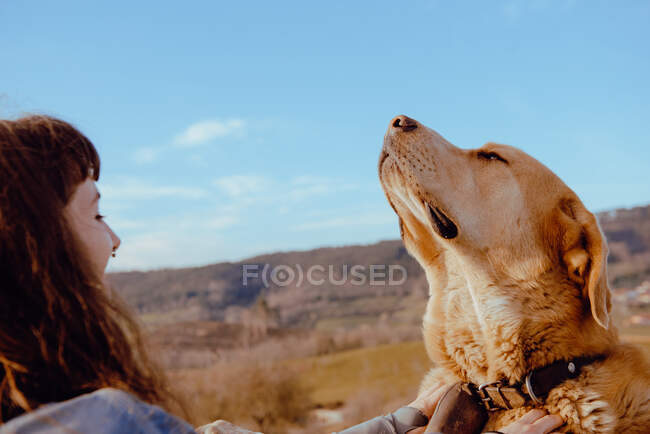 Side view of young hipster stroking funny dog between meadow and blue sky — Stock Photo