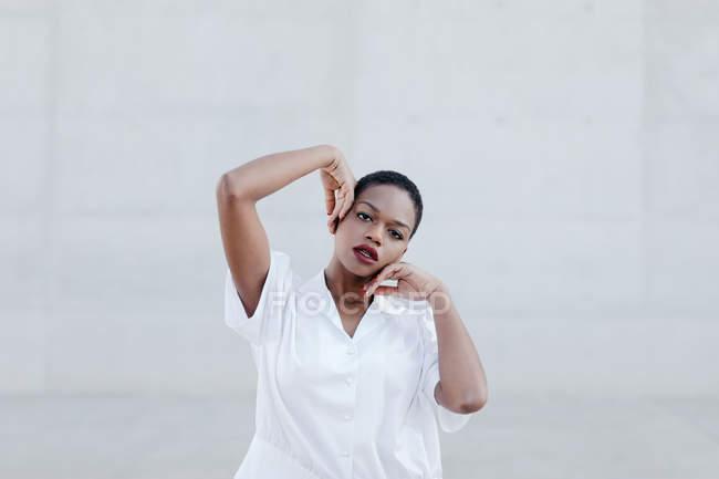 Mode à poil court femme ethnique en chemise blanche posant contre le mur gris — Photo de stock