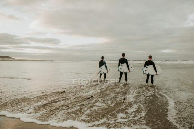 People with surfboard walking near sea — стокове фото