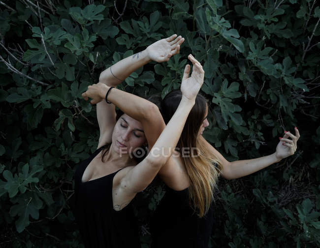 Side view of attractive young women with closed eyes and upped hands standing near green shrub — Stock Photo