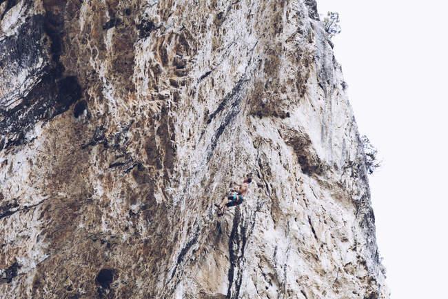 Vista laterale di un maschio irriconoscibile in pantaloncini che si arrampica su una ruvida scogliera nella giornata di sole in campagna — Foto stock
