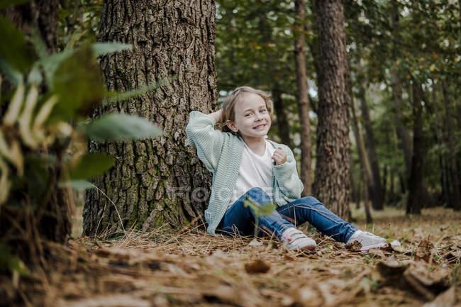 Positivo bambina seduta vicino albero nella foresta su sfondo sfocato — Foto stock