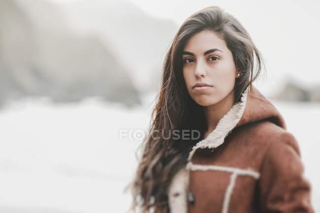 Retrato de mulher pensativa no casaco olhando para a câmera na costa perto de água no fundo borrado — Fotografia de Stock