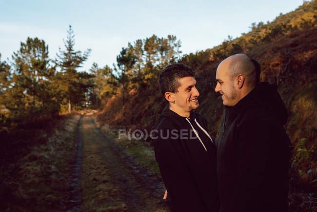 Счастливая гомосексуальная пара, обнимающаяся в лесу в солнечный день — стоковое фото