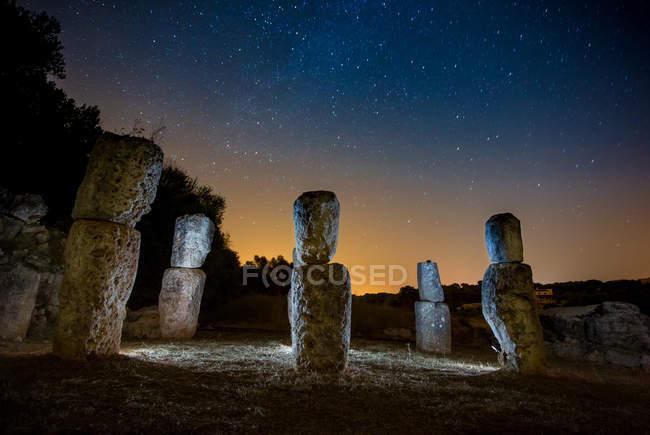 Скальные памятники, выделенные огнями и удивительное небо со звездами ночью — стоковое фото