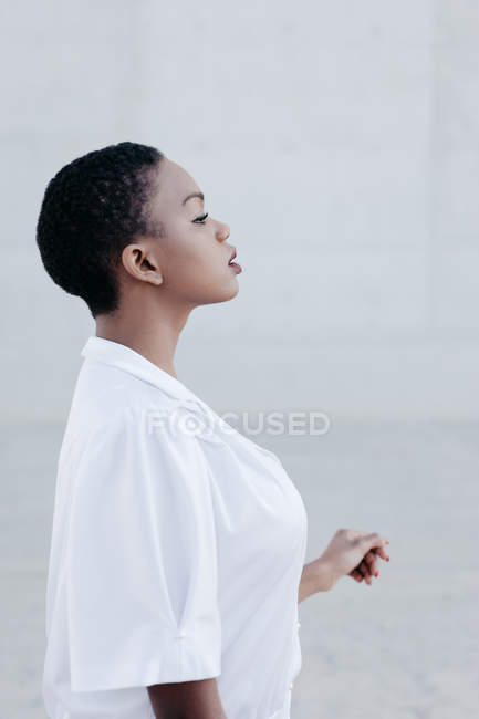 Profile of fashion short haired ethnic woman in white shirt posing against grey wall — Stock Photo