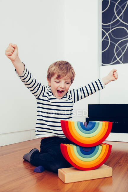 Blonde cute boy playing with waldorf rainbow puzzle — стокове фото