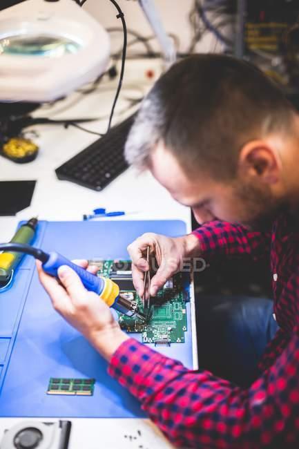 Nahaufnahme eines fokussierten Mannes, der die Hauptplatine seines Laptops am Arbeitsplatz repariert — Stockfoto