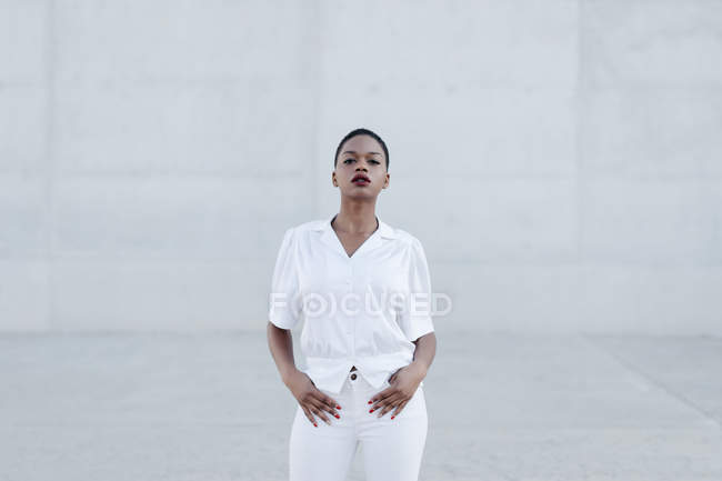 Fashion short haired ethnic model in white outfit posing against grey wall — Stock Photo