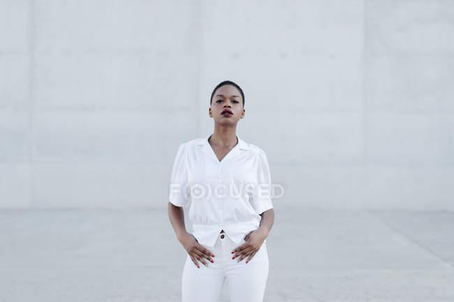 Moda modello etnico dai capelli corti in abito bianco in posa contro muro grigio — Foto stock