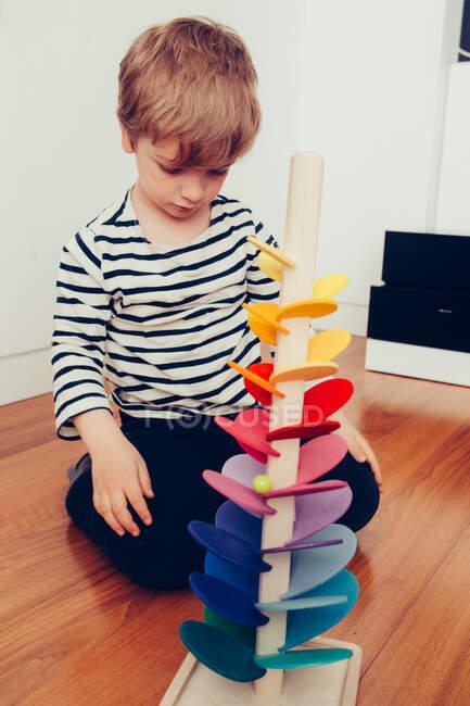 Bionda carino ragazzo giocare con waldorf suono torre con biglie — Foto stock