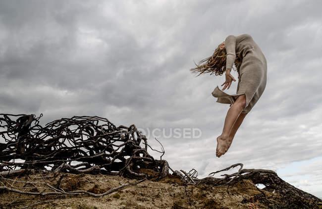 Desde abajo joven bailarina en vestido al aire libre cerca de ramas secas y cielo nublado - foto de stock