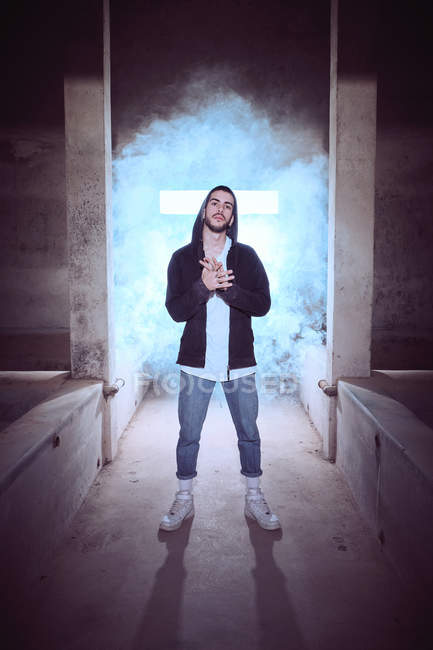Trendy confident guy standing in smoke — Stock Photo