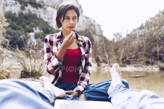 Homem deitado em xadrez com mulher sentada perto e mordendo morango até desfrutar de tempo juntos em piquenique na natureza — Fotografia de Stock