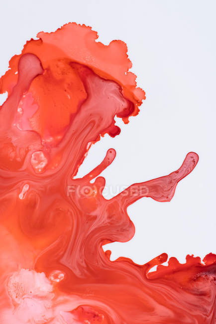 Abstraction of liquid paints in slow blending flow mixing together on white background — Stock Photo