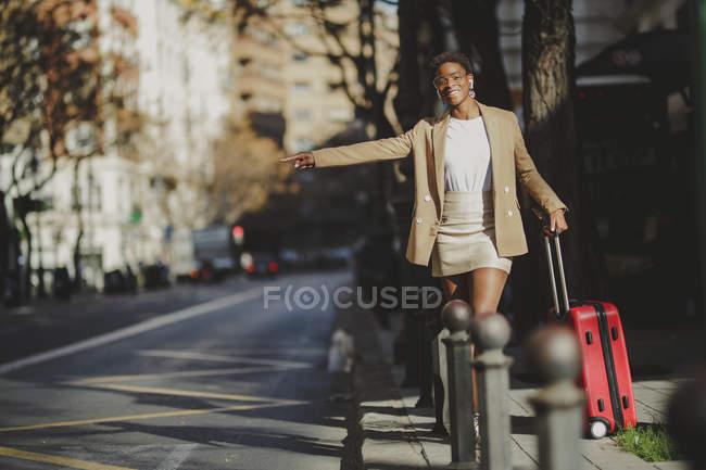 Femme élégante afro-américaine avec des bagages essayant d'arrêter une voiture près de la route en ville — Photo de stock