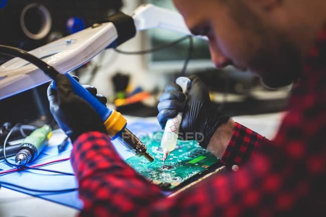 Nahaufnahme eines fokussierten Mannes, der Motherboard am Arbeitsplatz repariert — Stockfoto