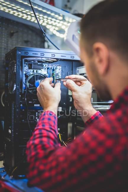 Nahaufnahme eines fokussierten Mannes, der PC am Arbeitsplatz repariert — Stockfoto