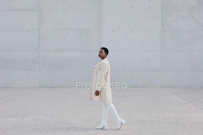 Mode kurzhaarige ethnische Frau im weißen Outfit vor grauer Wand — Stockfoto