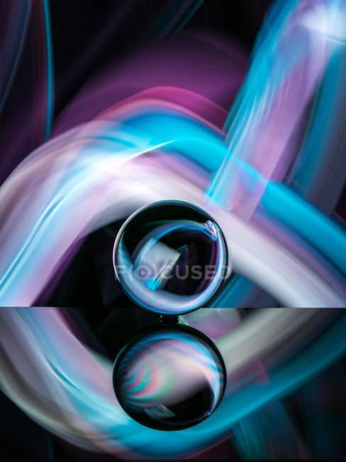 Хрустальный шар на поверхности с отражением вблизи абстрактных светит — стоковое фото