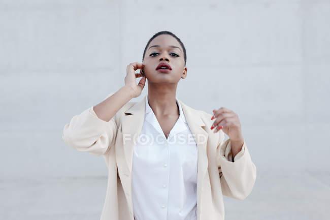 Мода короткий волосся етнічної жінки в білому Екіпіровка що створюють проти сірої стіни — стокове фото
