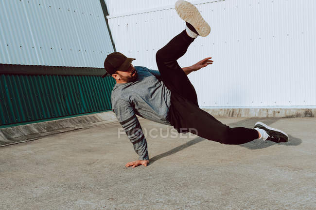Guy performing handstand while dancing near wall of modern building on city street — Stock Photo