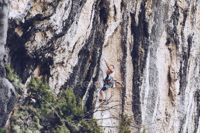 Vista laterale dell'uomo in pantaloncini arrampicata su ruvida falesia nella giornata di sole in campagna — Foto stock
