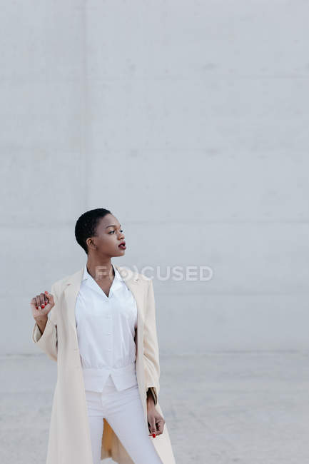 Mode kurzhaarige ethnische Frau in weißem Outfit posiert gegen graue Wand — Stockfoto