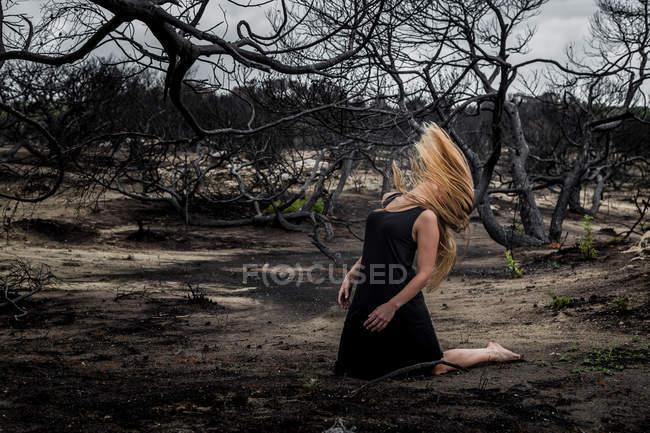 Young ballerina in black wear dancing on land between dry woods — Stock Photo
