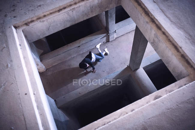 Anonymous man dancing in shabby building, high angle view — стокове фото