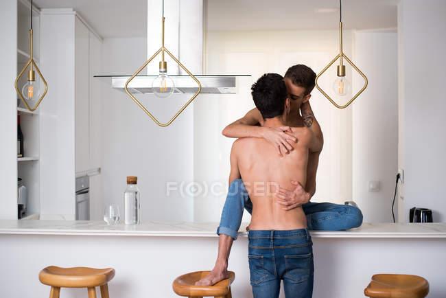 Пристрасні сексуальні сорочки пари геїв обіймаються в інтимний момент на кухонному столі — стокове фото
