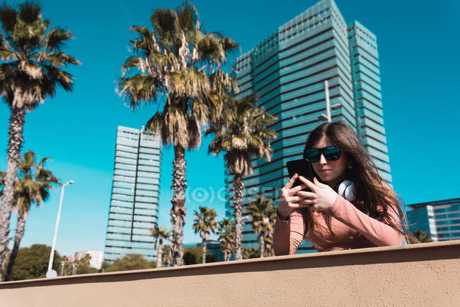 Teen girl looking at her smartphone on the street on a sunny day. - foto de stock