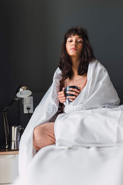 Young cozy woman with mug of drink wrapped in duvet sitting on bed in bedroom — Stock Photo