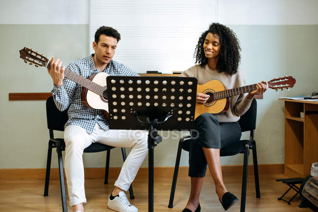 Young man and woman playing guitar during rehearsal in recording studio. — Stock Photo