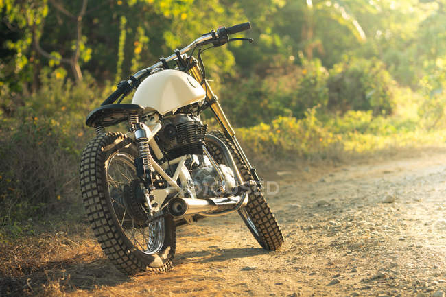 Motorcycle parked on path in countryside in sunlight — Stock Photo