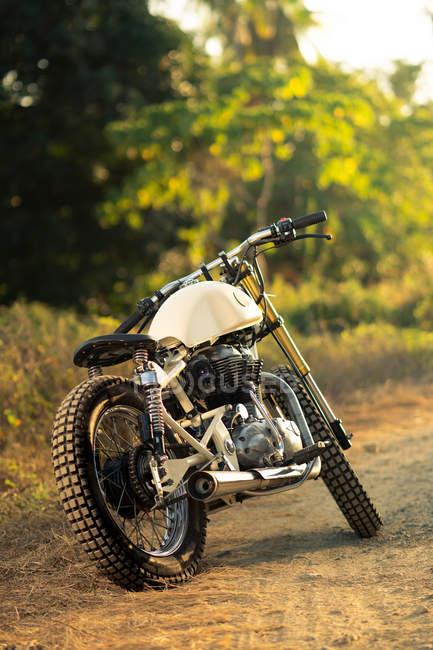 Motocicleta estacionada no caminho no campo à luz do sol — Fotografia de Stock