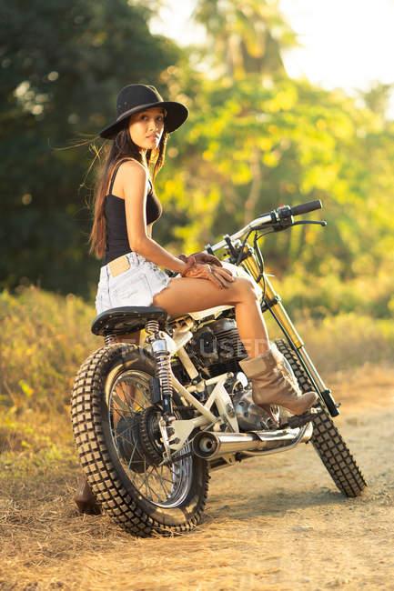 Attraktive asiatische Frau sitzt auf dem Motorrad auf dem Land — Stockfoto