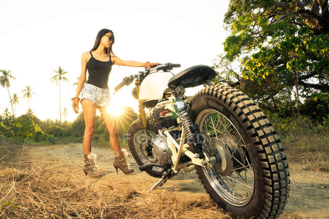 Attractive young woman in shorts and high-heeled boots standing with motorbike in backlit in countryside — Stock Photo