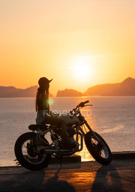 Silhouette de femme en chapeau assis sur moto sur la côte de la mer — Photo de stock