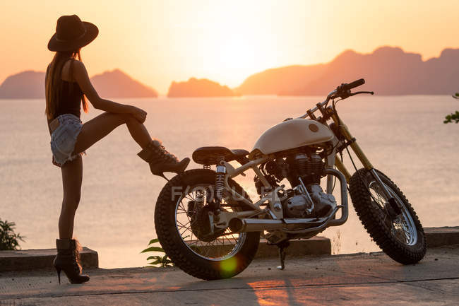 Woman in shorts, hat and high-heeled boots standing near motorcycle on sea coast — Stock Photo