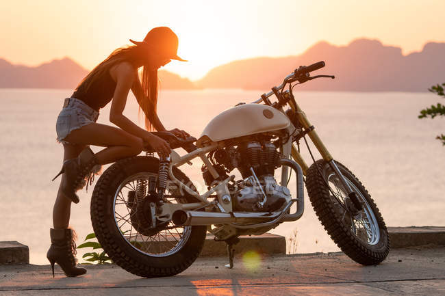 Woman in shorts, hat and high-heeled boots leaning motorcycle on sea coast — Stock Photo
